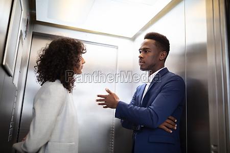 businesspeople having conversation in elevator