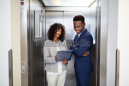 businesspeople discussing standing inside elevator