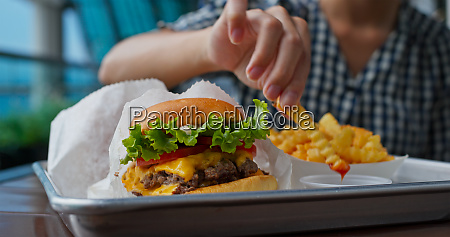 woman enjoy burger and french fries