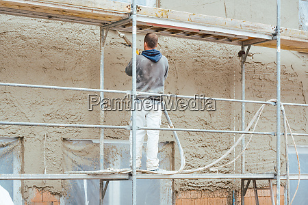 worker plastering outer wall of newly