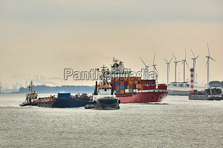 ship carrying containers through rotterdam