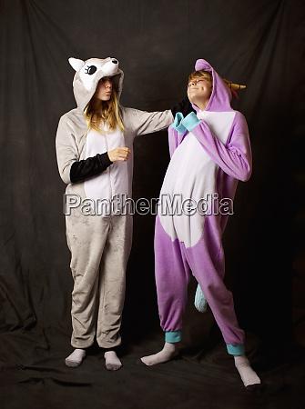 playful girls in animal costume pajamas