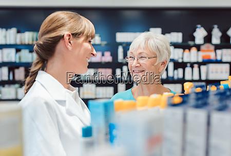 chemist and customer standing in pharmacy