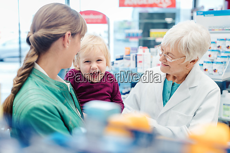 friendly pharmacist mother and child having
