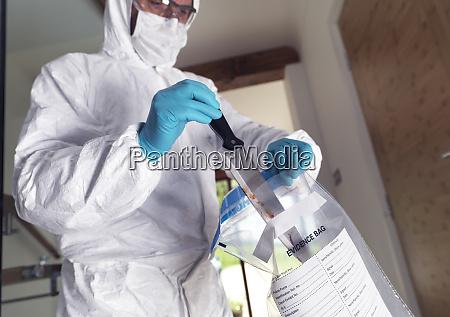 forensic scientist bagging a knife taken