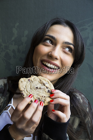 smiling woman looking sideways and eating