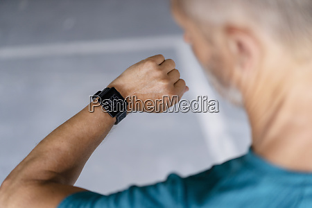 sporty man checking his smartwatch