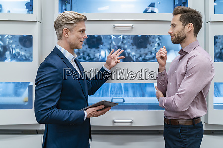 two businessmen with tablet talking at