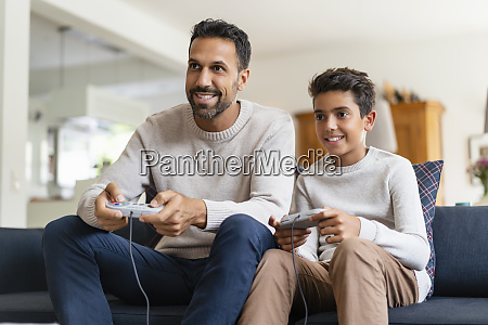 happy father and son playing video