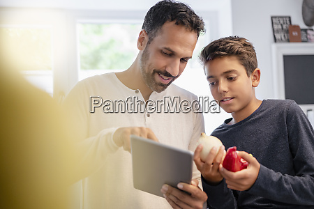father and son using tablet and