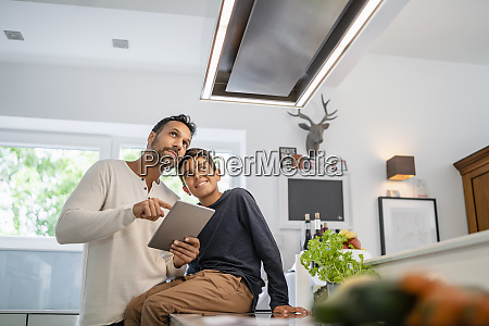 father and son using tablet in