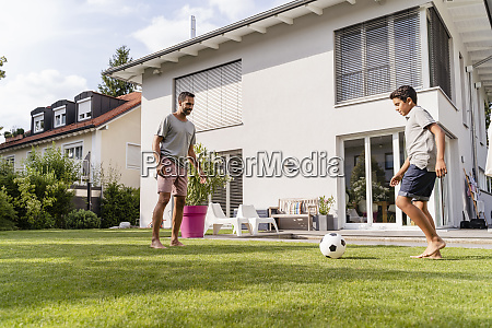 father and son playing football in