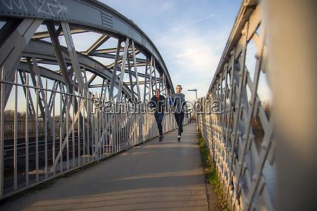 two teenagers running over railway bridge