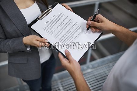 man signing employment contract in factory