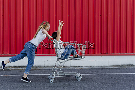 sisters with shopping cart in front