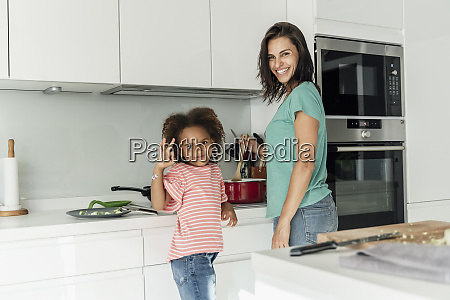 happy mother and daughter cooking in
