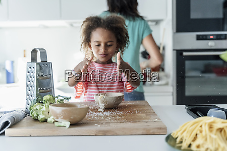girl playing with grated cheese in