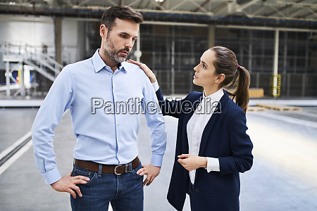 businesswoman talking to disappointed businessman in