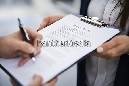 close up of employee signing employment