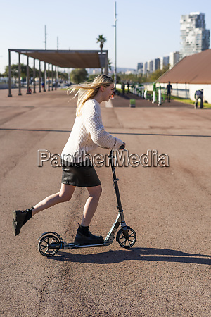 smiling young woman riding kick scooter