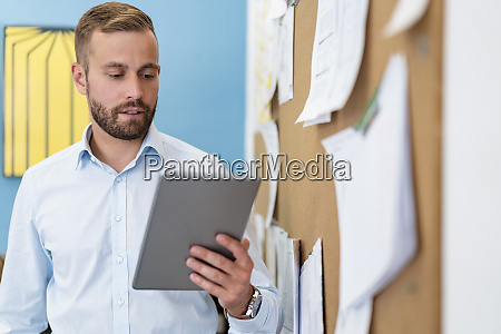 businessman using tablet at pinboard in
