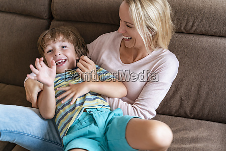 playful mother and son on couch