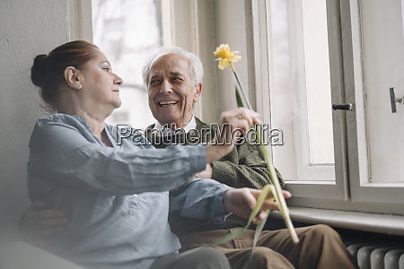 happy senior couple with flower at