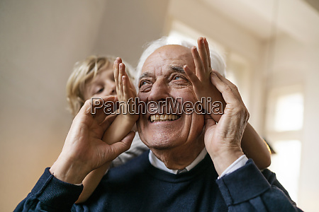 playful grandson with grandfather at home