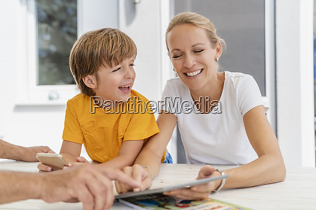 happy mother and son doing homework