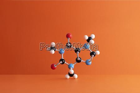 caffeine formulas molecular structure over orange