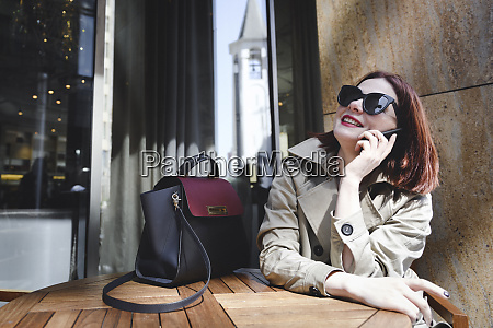 businesswoman sitting outdoors making phone calls
