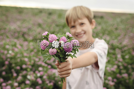 smiling boy giving clover flowers