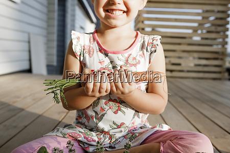 little girl sitting on terrace holding