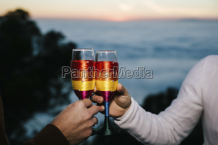 gay couple clinking champagne glasses wrapped