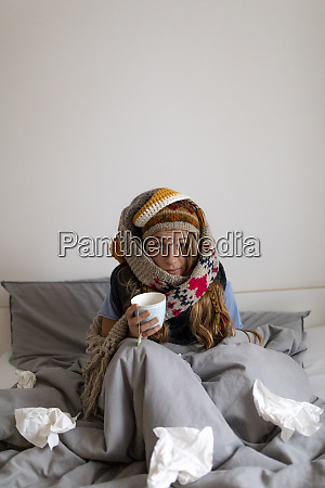 ill young woman drinking tea in