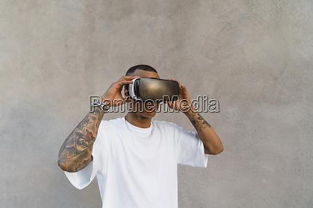 tattooed young man using virtual reality