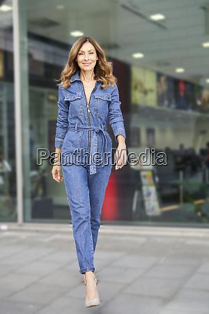 mature woman wearing denim jumpsuit