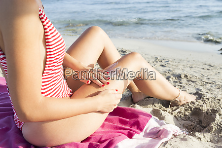 woman sitting on the beach putting