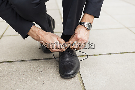 businessman tying his shoe on pavement