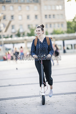 young woman riding electric scooter in