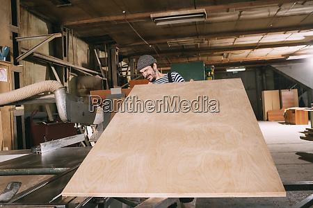 carpenter checking wooden board