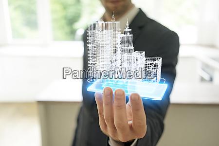 businessman holding hologram of architectural model