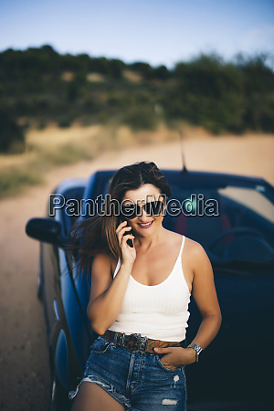 sexy woman leaning on convertible using