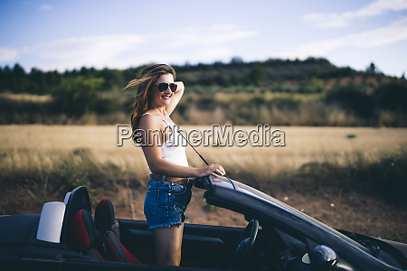 woman standing in her convertible looking