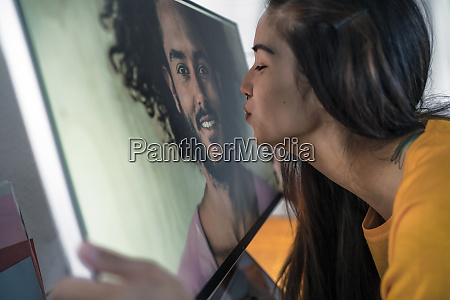 young woman kissing man on computer