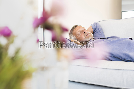 senior man lying on couch at
