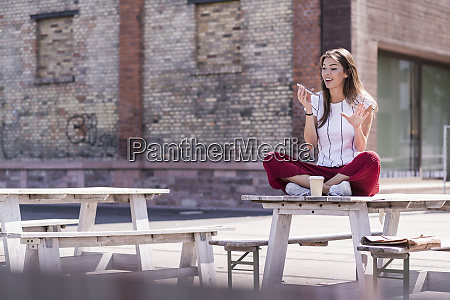 young woman sitting on table in