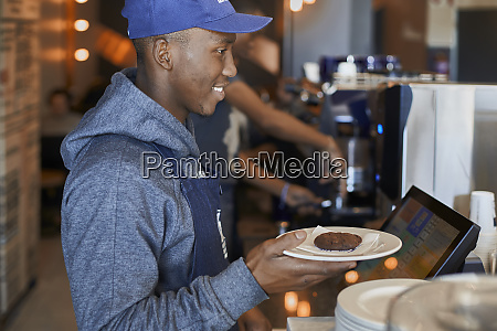 young man serving a cookie to