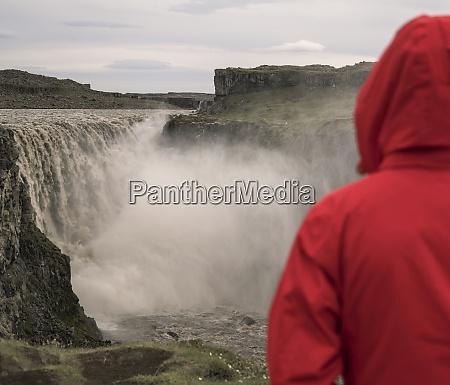 young woman looking at dettifoss waterfalls