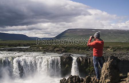 man looking at godafoss waterfalls iceland